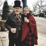 two people in victorian cosumes handing out hot drinks